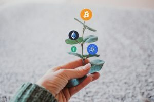 A plant with cryptocurrency symbols on branches