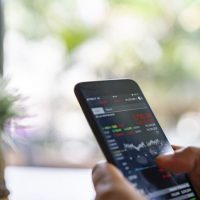 Businesswoman trading stocks with Phone