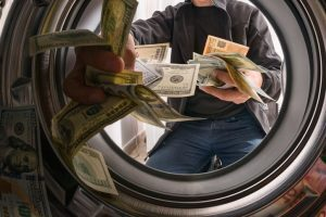 money being thrown into a laundry machine indicating money laundering